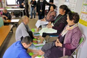 被災者の仮設住宅で、脚をマッサージする僧侶たち=2014年3月、宮城県亘理町、小林孝明さん提供