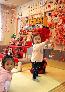 つるしびなとひな飾りの周りで遊ぶ女の子たち=岩沼市桑原4丁目の岩沼みなみプラザ