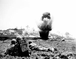 日本軍の壕(ごう)がダイナマイトで爆破されるのを見つめる米兵(1945年、沖縄県公文書館提供)
