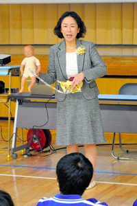 赤ちゃんの人形を使い、妊娠・出産について説明する直井亜紀さん=三郷市の彦成中学校