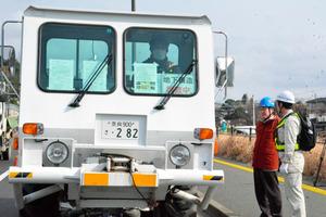 揺れを起こす電源車の前で調査について話す九大の清水洋教授(左)ら=熊本市西区