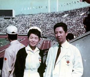 看護師として五輪開催中の国立競技場に派遣された村尾イミ子さんと医師の真俊さん。2人は1カ月後に結婚式を挙げた=1964年10月、東京都、村尾イミ子さん提供
