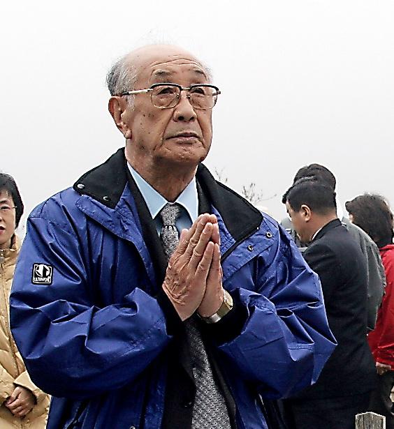国後島の日本人墓地を訪れ、慰霊する小泉敏夫さん=2005年5月