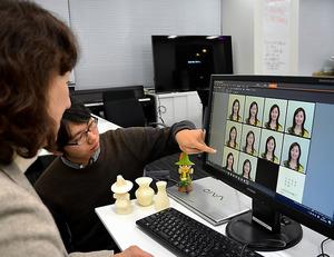顔画像美観化処理システムを使いながら、互いにいいと感じる画像について、荒川薫教授(左)と学生が話し合う