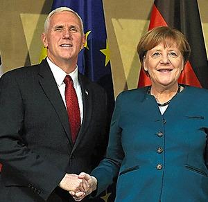 18日、会談前に握手するペンス米副大統領(左)とドイツのメルケル首相=AFP時事