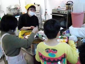 子どもたちにカレーを盛る伊藤睦美さん(奥)=池田市豊島北1丁目、中野晃撮影