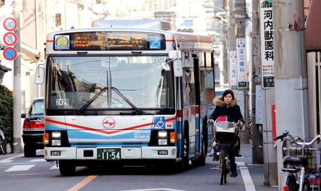 電柱が林立するバス通り。自転車をよけようとバスが中央線を大きくはみ出した=8日午後、東京都大田区大森南、飯塚晋一撮影(電柱にモザイクをかけています)