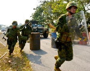 訓練で小銃や盾を持ち、走ってバリケードを突破する自衛官ら。後ろの車列には保護した日本人らが乗るワゴン車がある=19日、タイ中部の同国軍基地、福井悠介撮影