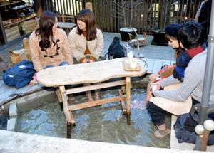 お客がカフェの足湯につかる=神奈川県箱根町宮ノ下