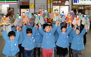 自分たちで顔を描いた「うちわびな」を掲げる子供たち=JR丸亀駅