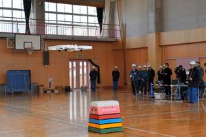 東京電力福島第一原発に導入予定のドローンの試験飛行をする東電関係者ら=楢葉町
