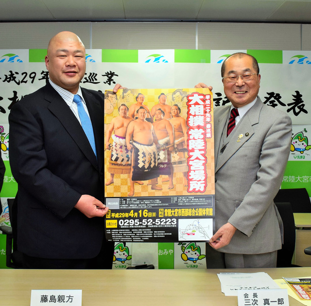 4横綱を並べて作り直したポスターを掲げ、常陸大宮場所をPRする藤島親方(左)と三次真一郎市長=常陸大宮市