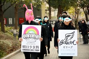 マスクをつけて国会周辺を行進する「明日少女隊」などのメンバーたち=東京都千代田区