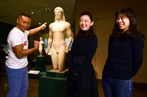 クーロス像の前で語るプロレスラーのCIMAさん(左)と女子組読者の2人。奥に見えるのがコレー像=小林一茂撮影