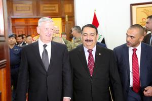 バグダッドのイラク国防省で20日、並んで歩くマティス米国防長官(左)とイラクのハヤリ国防相(右から2人目)=ロイター