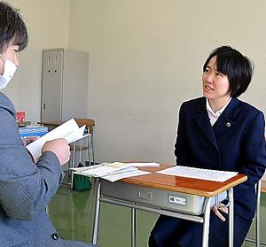 教室で担任の阿部圭一教諭と卒業式の打ち合わせをする菊池歩実さん=福島県いわき市の双葉高校