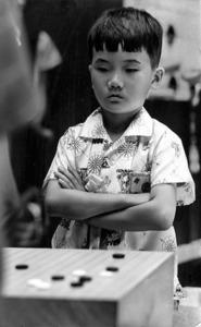 来日翌日の林海峰六段との公開対局。早打ちでポカしないよう、腕組みして考えるよう兄に言い含められて臨んだという=1962年8月2日、東京都千代田区のサンケイホール