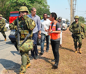 小銃を持った陸上自衛隊員に警護されながら、空港へ向かう米国人ら=19日、タイ中部のウタパオ海軍航空基地、福井悠介撮影