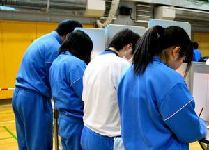 記載台で投票用紙に記入する生徒たち=東京都足立区花畑7丁目の足立特別支援学校、円山史撮影