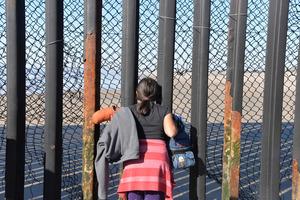 メキシコ・ティフアナで、国境の鉄柵から米国側をのぞき込む少女。この後、少女は足元の金網の破れ目から米国側に渡った=1月28日、田村剛撮影