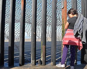 メキシコ・ティフアナで国境の鉄柵前に立つ少女。この後、少女は足元の金網の破れ目から米側に渡った=1月28日、田村剛撮影