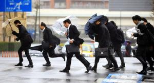 強い雨風の中、出勤する人たち=23日午前、横浜市西区、長島一浩撮影