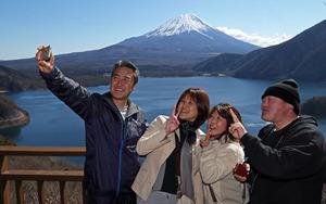 展望デッキで千円札の図柄を背景に記念写真を撮る行楽客=19日、身延町中ノ倉