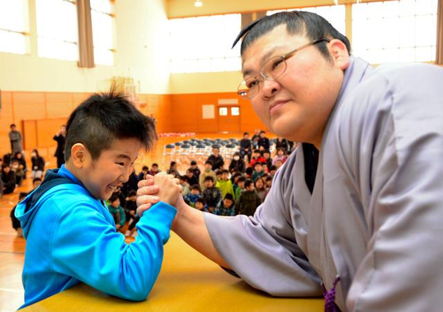 豪風関と腕相撲をする小学生=秋田市保戸野すわ町の保戸野小学校