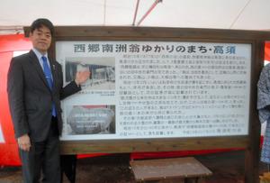 設置された「西郷南洲翁ゆかりのまち・高須」の案内板。左は西郷隆夫さん=鹿屋市