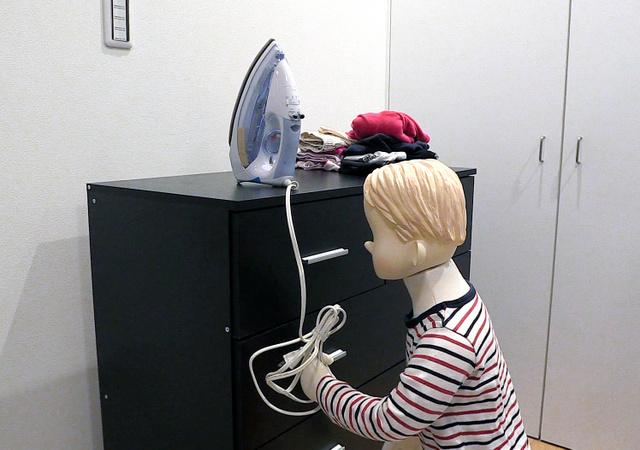 子どもがアイロンの電源コードに興味を示して、引きずり下ろしてしまうイメージ(NITE提供)