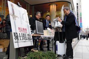 朝の通勤時間帯にあわせ、村上春樹さんの新刊「騎士団長殺し」が販売されていた=24日午前7時40分、東京都中央区、角野貴之撮影