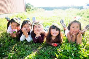 熊本地震の約2週間後、ビニールハウスの中のテントで避難生活を送っていた子どもたちを撮った川端麻衣さんの作品。学校が再開されない中、遊び場になっている草地で笑顔を見せた(熊本県益城町、川端さん提供)