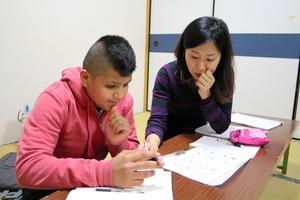 平仮名の書き方をボランティアの女性に習うジェレミーさん=大阪市西淀川区