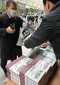 朝の通勤時間帯にあわせ、村上春樹さんの新刊「騎士団長殺し」が販売されていた=24日午前7時32分、東京都中央区、角野貴之撮影