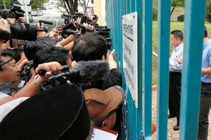マレーシアの首都クアラルンプールにある北朝鮮大使館で24日、門の前に集まった報道陣に声明を読み上げる北朝鮮領事=AP