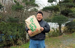 収穫した米俵をかかえる米農家の横田和希さん=福島県広野町