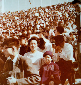 夫の功さんのカメラを前に、はにかむ青山敬子さんと、一張羅のワンピース姿の長女康子さん=1964年10月、東京都新宿区、青山さん提供