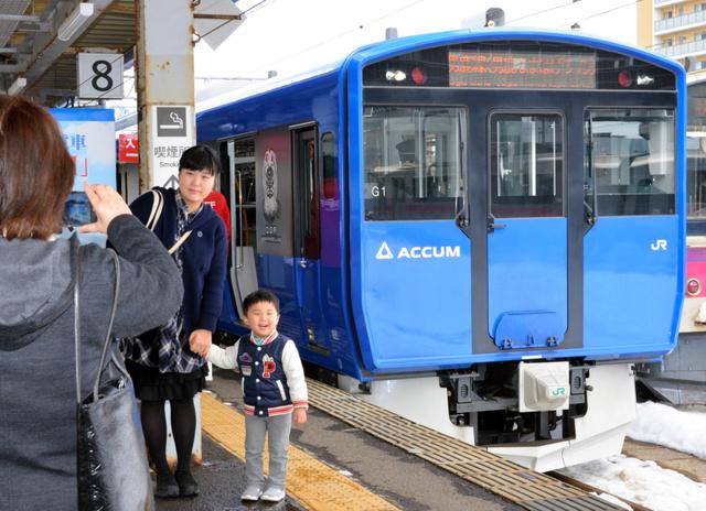 蓄電池電車「ACCUM」の前で記念撮影する人たち=JR秋田駅