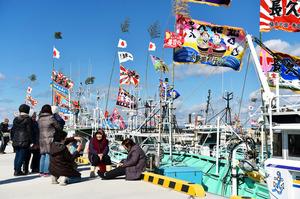 請戸漁港に戻った漁船の前では、記念撮影をする家族の姿があった=25日、浪江町請戸、福留庸友撮影