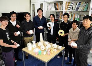 折り紙作品を手にする三谷純教授(右から4人目)と研究室の学生ら=茨城県つくば市の筑波大学