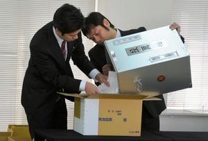 投票箱に入ったままだった住民投票の投票用紙を保管用の段ボール箱に移す市職員ら=輪島市役所