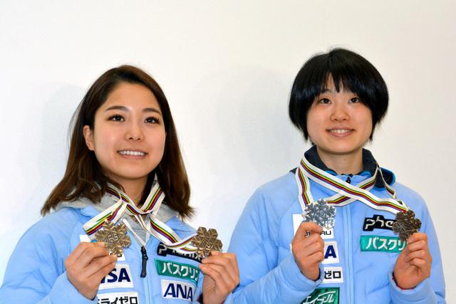 帰国した成田空港でメダルを掲げて撮影に応じる高梨(左)と伊藤
