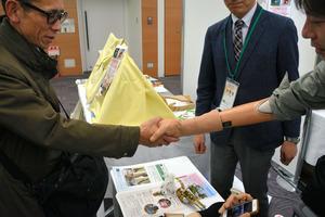 筋電義手の試作品を動かし、発表イベントの来場者と握手を交わす記者(右)=東京都江東区のTOC有明