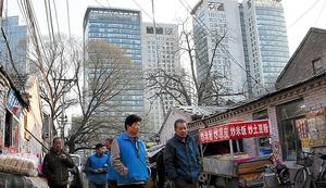 貧富の格差を象徴する北京市中心部の化石営地区。高層ビルが立ち並ぶビジネス地区の中に、粗末な平屋の家が並ぶ=2月23日、延与光貞撮影