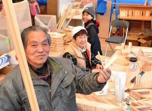「つみき」が作られている作業場で、完成品と材料の板を持つ那須社長=美郷町