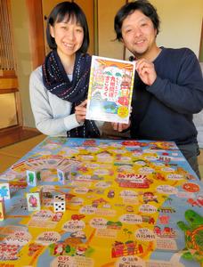 「ぐるっと一周!九州開運すごろく」を発刊した燦燦舎の鮫島亮二さんと妻のさめしまことえさん=鹿児島市