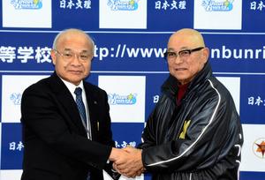 会見後、握手を交わした日本文理高校の大井道夫監督(右)と上野順治校長=新潟市西区新通