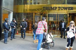 トランプタワー正面で重装備で警備するニューヨーク市警の警官ら(左)と、出入りする人たち=2月24日午後、ニューヨーク