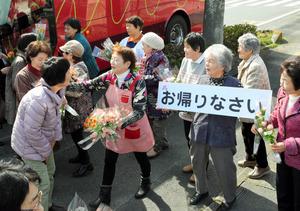 「お帰りなさい」と被災者らを迎える人たち=加須市正能の加須ふれあいセンター