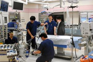 模擬手術の準備をする県立医大のチーム。麻酔をかけた生きた豚を手術台に載せたという=郡山市富田町